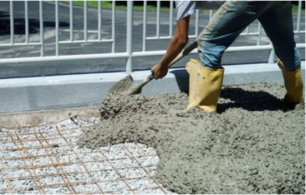 man shovel cement into flat work form
